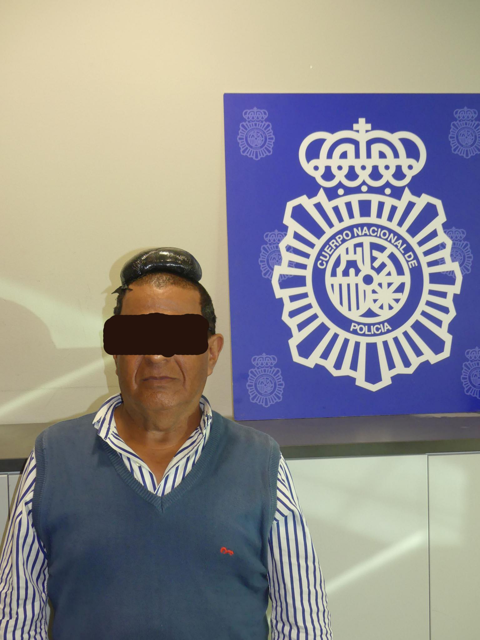 A man poses with a drug package on his head, that he hid under a toupee, after being arrested in Barcelona