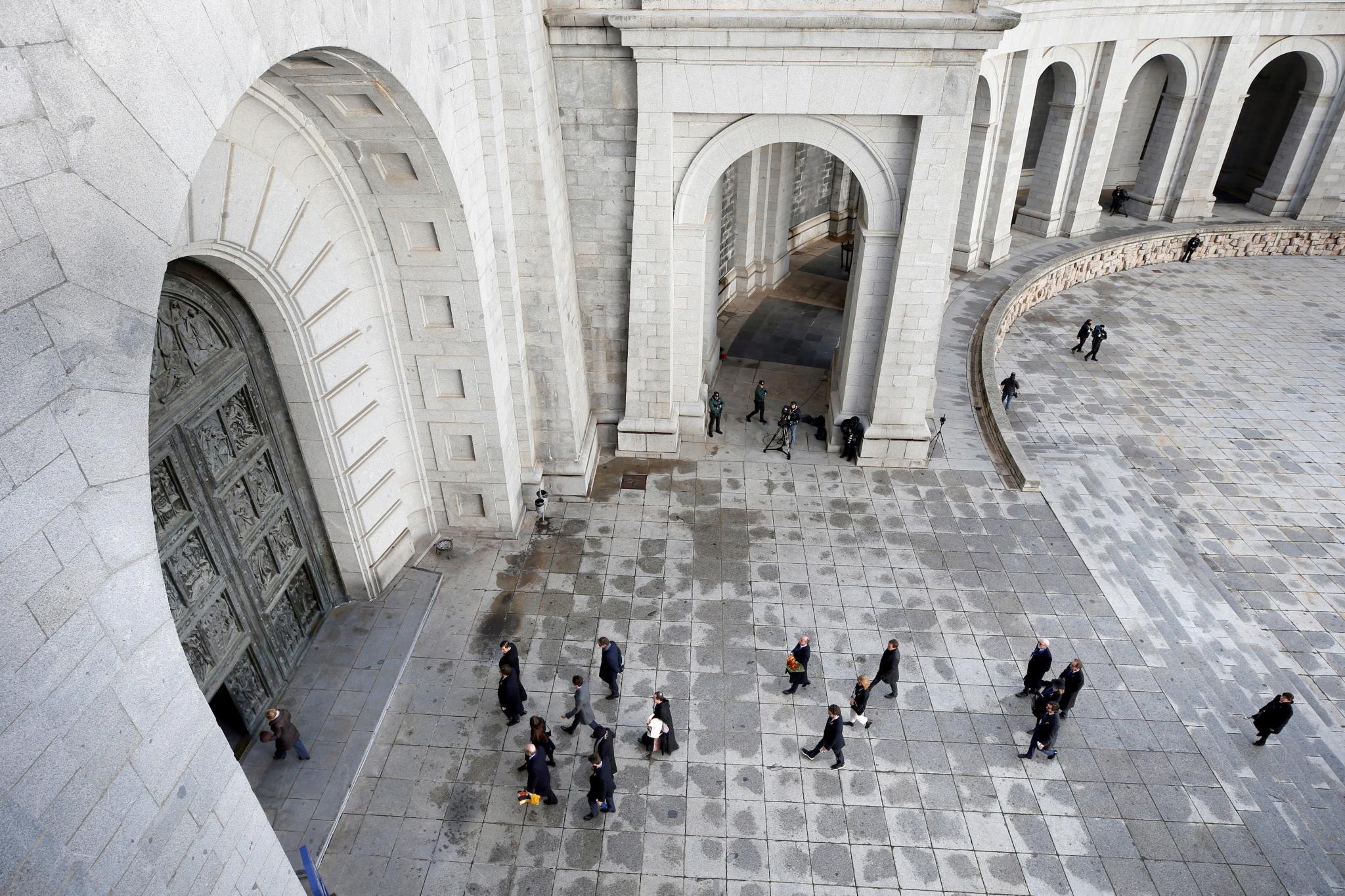 Los familiares de la familia Franco acompañados por el prior de la basílica del Valle de los Caídos, Santiago Cantera, acceden al templo para asistir a la exhumación de los restos del dictador en la basílica, donde están presentes las autoridades qu