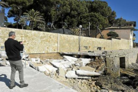 A tourist takes a photograph of the storm damage in Cala Gat.