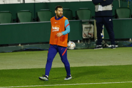 Barcelona's Lionel Messi warms up from the substitutes bench