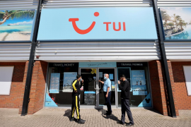 People stand outside the TUI travel center