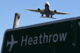 A plane passes a sign as it comes into land at Heathrow Airport