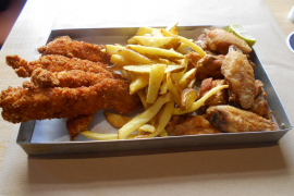 Breaded chicken fingers, deep-fried chicken wings and chips as served at Buco Burger in a traditional llauna