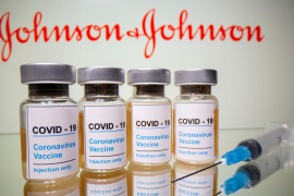 Vials and medical syringe are seen in front of J&J logo in this illustration
