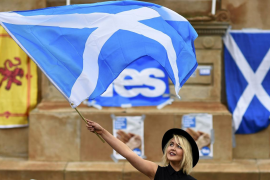 A woman waves a Scottish Saltire
